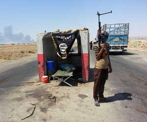 An ISIL militant stands guard at a checkpoint outside the Beiji refinery, on June 19, 2014.