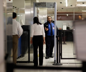 A TSA officer directs a traveler to step through a metal detector at BWI-Marshall Airport in Linthicum, Md.