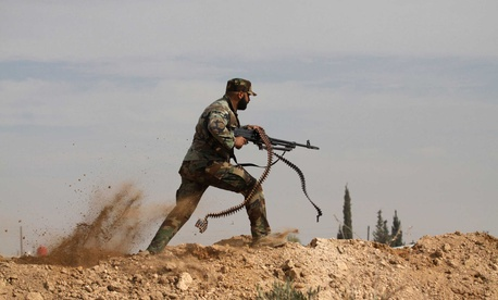 An Iraqi Shiite fighter clashes with members of the Sunni Free Syrian Army in Hatita, on November 22, 2013.
