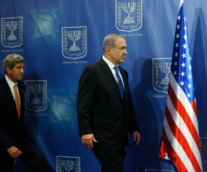 Israeli Prime Minister Benjamin Netanyahu walks on stage with Secretary of State John Kerry for a photo opportunity before a meeting in Tel Aviv on July 23, 2014.