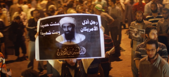 Egyptian Salafis hold posters of former al-Qaeda leader Osama Bin Laden in front of security headquarters in Cairo, Egypt.