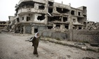 A woman walks through a devastated part of Homs, Syria, on June 5, 2014.