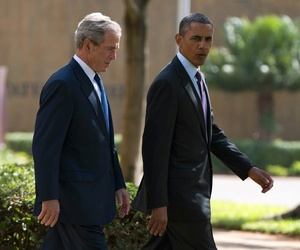 President Barack Obama, right, walks with former president George W. Bush during a wreath laying ceremony to honor the victims of the U.S. Embassy bombing on July 2, 2013, in Dar es Salaam, Tanzania.