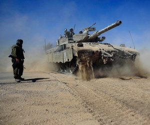 Israeli reservists direct a Merkava tank as it advances towards the border between Israel and Gaza.