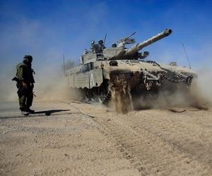 Israeli reservists direct a Merkava tank as it advances towards the border between Israel and Gaza.