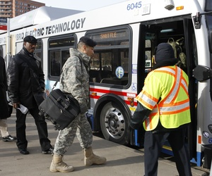 Military and civilian employees prepare to board a bus bound for the Pentagon.