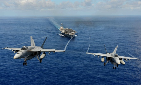 Two F/A 18s with the Strike Fighter Squadron 14 participate in a demonstration over the USS John C. Stennis.