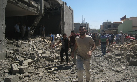 Iraqis inspect the site of a double car bomb attack in Kirkuk, Iraq on August 7, 2014.