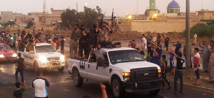 Militants with the Islamic State of Iraq and the Levant parade in the northern city of Mosul, Iraq, on June 25, 2014.