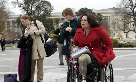 Rep. Tammy Duckworth, D-Ill., an Iraq War veteran who lost both legs in combat before turning to politics, arrives for a group photo on the East steps of the Capitol in Washington, Thursday, Nov. 15, 2012. (AP Photo/Susan Walsh)