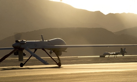 An MQ-1B Predator and an MQ-9 Reaper taxi to the end of a runway at Creech Air Force Base in preparation for takeoff, on June 13, 2014.