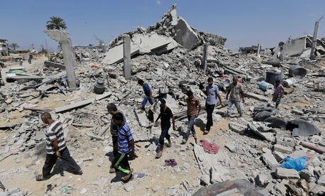 Palestinians in Khuzaa, in the southern part of the Gaza Strip, walk on the rubble of houses destroyed by Israeli strikes.