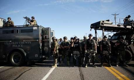 Police in riot gear watch protestors in Ferguson, Mo., on August 13, 2014.