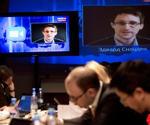 Edward Snowden, displayed on television screens, asks a question to Russian President Vladimir Putin during a nationally televised question-and-answer session, in Moscow, Thursday, April 17, 2014.
