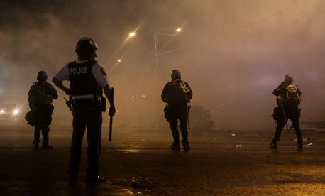 Law enforcement officers watch as tear gas is fired to disperse a crowd protesting in Ferguson, Mo., on Saturday.