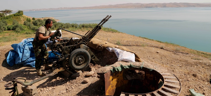 A Kurdish peshmerga fighter prepares his weapon at his combat position near the Mosul Dam at the town of Chamibarakat outside Mosul, Iraq, Aug 17, 2014.