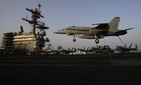 An F/A 18 Hornet coming from Iraq lands on the flight deck of the USS George H.W. Bush on August 10, 2014.