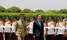 Syria's President Bashar Assad, reviews an honor guard upon his arrival at the presidential palace to take the oath of office for his new term of office, on July 16, 2014.