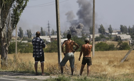 Local residents watch as smoke rises during shelling in Novoazovsk in eastern Ukraine.