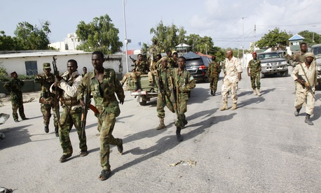 Somali soldiers patrol near the wreckage of a car bomb that detonated in Mogadishu, on July 9, 2014.