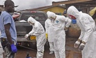 Health workers in Monrovia, Liberia, remove their protective clothes after carrying the body of a woman who may have died from the Ebola virus, on September 10, 2014.