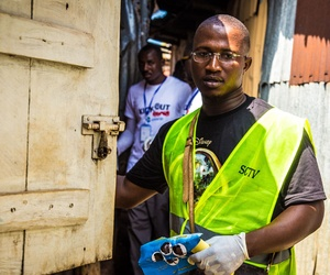 A health worker volunteers distribute bars of soap and information about Ebola in Freetown, Sierra Leone, Saturday, Sept. 20, 2014.