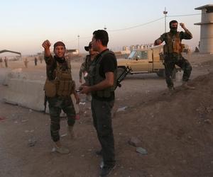 Kurdish Peshmerga fighters react during airstrikes target Islamic State militants near the Khazer checkpoint outside of Erbil, Iraq.