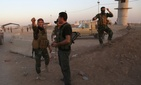 Kurdish Peshmerga fighters react during airstrikes target Islamic State militants near the Khazer checkpoint outside of Erbil, Iraq.