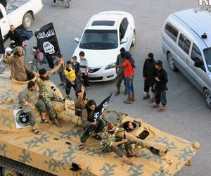 This undated image posted by a Syrian opposition group, on June. 30, 2014, which has been verified and is consistent with other AP reporting, shows fighters from the al-Qaida linked ISIL sitting on their tank during a parade in Raqqa, Syria.