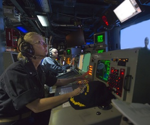 The commanding officer of the USS Arleigh Burke observes operations in the combat information center.