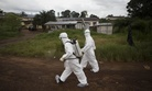 Healthcare workers in Sierra Leone spray disinfectant to prevent the spread of the Ebola virus in Kenema, on September 24, 2014.