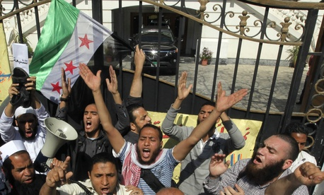 Ultraconservative protestors wave a Syrian revolution flag outside the residence of Iran's ambassador to Egypt.