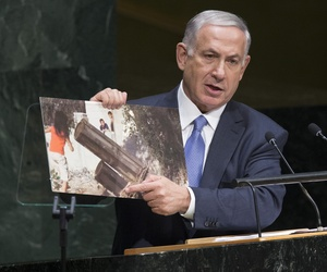 Israel's Prime Minister Benjamin Netanyahu, during a speech at the U.N. General Assembly, points to a photo that he says shows rocket launchers in residential neighborhoods in Gaza.