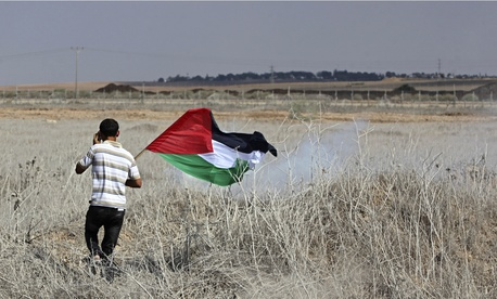 A protestor carries a Palestinian flag during clashes with Israeli forces after a protest at the Nahal Oz crossing, east of Gaza City, on September 27, 2013.
