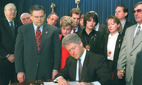 President Clinton signs into law the Helms-Burton bill while Members of Congress look on, on March 12, 1996.
