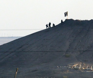 In this telephoto image shot through haze from the outskirts of Suruc at the Turkey-Syria border, ISIL militants are seen after placing their group's flag on a hilltop at the eastern side of the town of Kobani, Syria, Oct. 6, 2014.