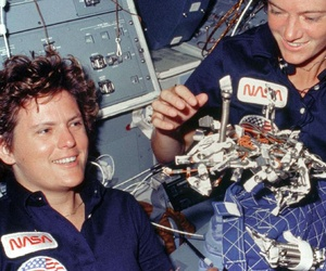 "Astronauts Kathryn D. Sullivan, left, and Sally K. Ride display a ""bag of worms"" during the STS-41G mission in 1984. The bag is a sleep restraint and the majority of the 'worms' are mostly springs and clips used with the sleep restraint."