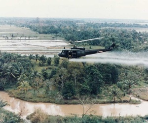 A U.S. Army Huey helicopter sprays Agent Orange over Vietnamese agricultural land.