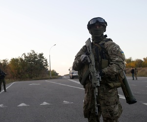 A Ukrainian soldier stands guard at a road near the town of Donetsk, on September 20, 2014.