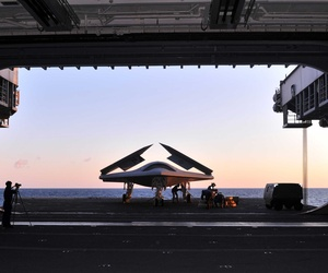 An X-47B Unmanned Combat Air System demonstrator is loaded on an aircraft elevator aboard the USS George H.W. Bush, on May 14, 2014.
