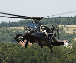 Two soldiers from the Multi-National Task Force ride on an Ah-64 Apache helicopter during an exercise at Camp Bondsteel, Kosovo.