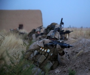 A Marine Corps corporal takes cover behind a berm during a firefight in Helmand Province, Afghanistan, on July 6, 2014.