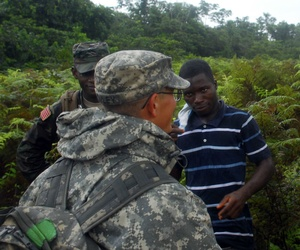 U.S. military personnel discuss construction details with a Liberian contractor at the future location of an Ebola treatment unit in Liberia.