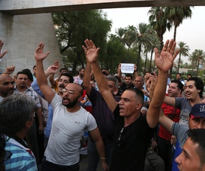 People chant anti-terrorism slogans to protest the Islamic State's blockade, in Baghdad's Tahrir Square, on August 28, 2014.