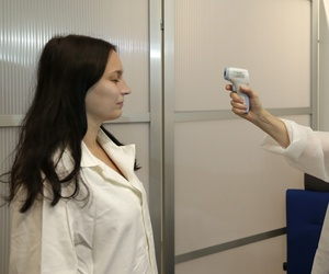 Medical staff demonstrate how to take the temperature of a passenger at Vaclev Havel Airport in Prague, Czech Republic.