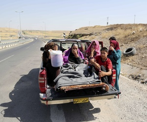 Displaced Iraqis ride on a truck on a mountain road near the Turkish-Iraq border, outside of Dahuk, on August 9, 2014.