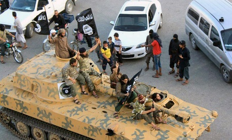 ISIS fighters sit on their tank during a parade in Raqqa, Syria.