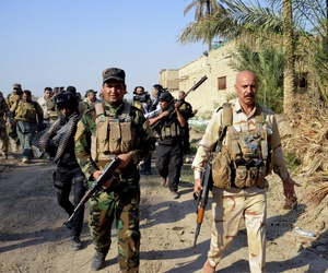 Iraqi security forces and Shiite militiamen patrol Jurf al-Sakhar, 43 miles south of Baghdad, on October 25, 2014.