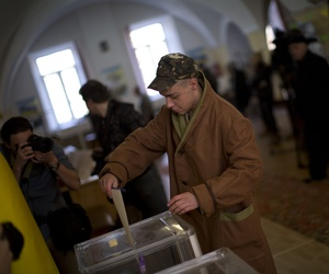 A Ukrainian soldier casts his vote for the parliamentary election at a polling station in a military hospital in Kiev, Ukraine