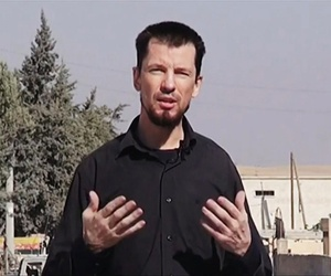 In this screenshot, British journalist John Cantlie speaks into a camera in what he identifies as the Syrian town of Kobani while talking about airstrikes on the town.